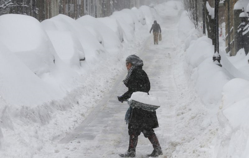 A woman shovels snow on Joy Street during a winter blizzard in Boston, Massachusetts in this February 15, 2015, file photo. REUTERS/Brian Snyder/Files