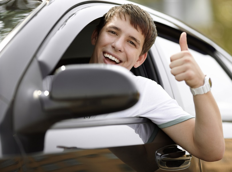 teen driver in good mood with black car, selective focus on eyes