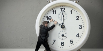 Businessman pulling a clock hand backwards,time