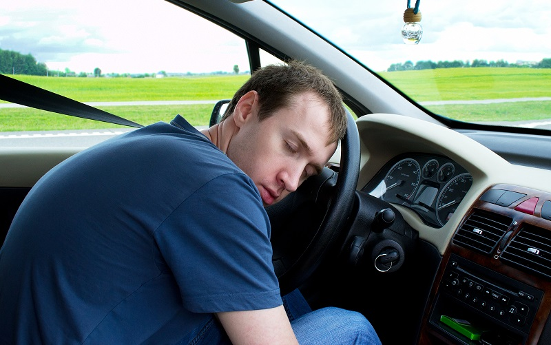 The young man sleeps in the car