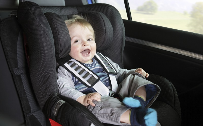 Safety in the car - Smiling baby boy safely sitting in a car seat