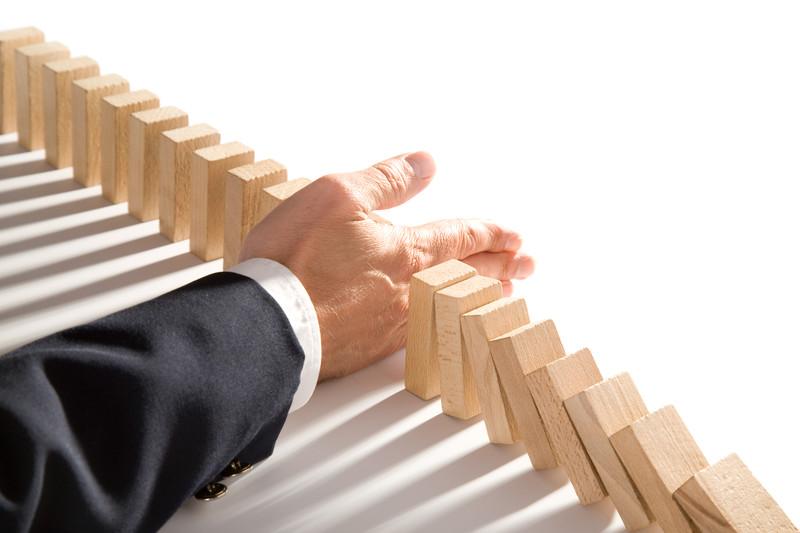 businessman-interrupting-wooden-dominoes