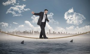 Mature businessman doing a balancing act against cityscape on horizon over shark infested sea