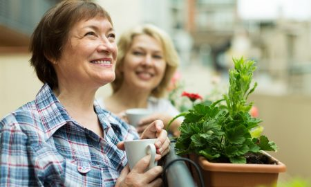 Smiling senior women staying on balcony with cup of coffee in hands