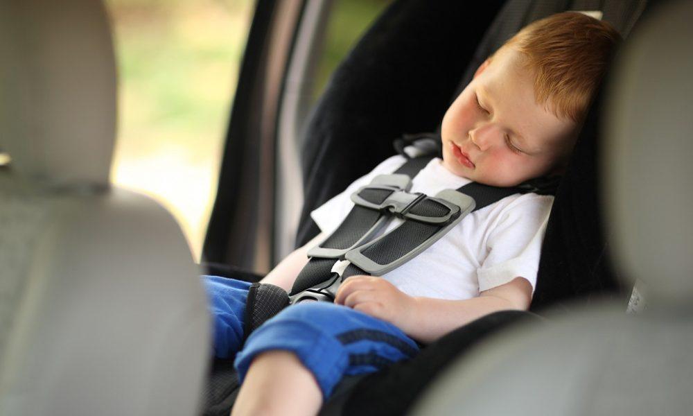Boy sleeping in child car seat. Shallow DOF.