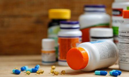 medicine-bottles-and-tablets-on-wooden-desk_1387-420