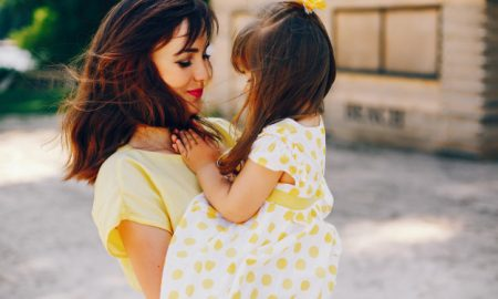 on-a-sunny-beach-with-yellow-sand-mom-walks-in-a-yellow-dress-and-her-little-pretty-girl