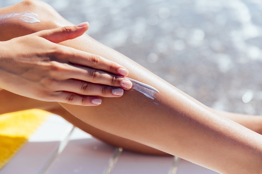 Close-up view of female hand applying sunscreen on her leg, near the sea. Healthcare.