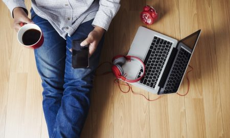 Soft photo of man felling comfort use smartphone on the wooden floor with cup of coffee, headphone, computer laptop and clock, Top view point of copyspace relax time.