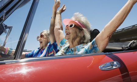 Two senior women in convertible car, arms outstretched, side view