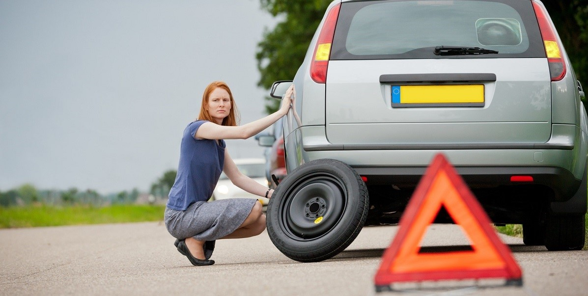 A female driver about to fix a flat tire on her station wagon car.