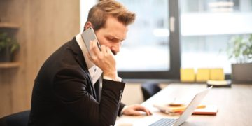man-having-a-phone-call-in-front-of-a-laptop-insurancedaily