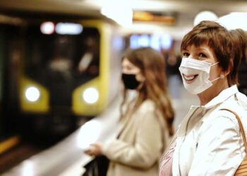 Passengers with face masks wait for a train at the Alexanderplatz underground station in Berlin, Germany, Monday, April 27, 2020. In order to contain the coronavirus, it is mandatory to wear a cover for mouth and nose at public transport at the German capital. (Kay Nietfeld/dpa via AP)