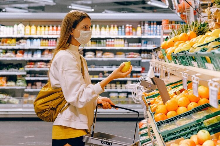 woman-in-yellow-tshirt-and-beige-jacket-holding-a-fruit-insurancedaily