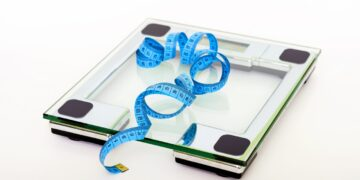blue-tape-measuring-on-clear-glass-square-weighing-scale