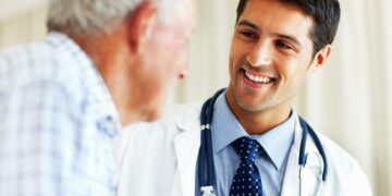 Elderly man receiving advice from male doctor