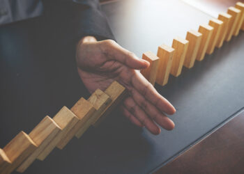 problem-solving-close-up-view-hand-business-woman-stopping-falling-blocks-table-concept-about-taking-responsibility