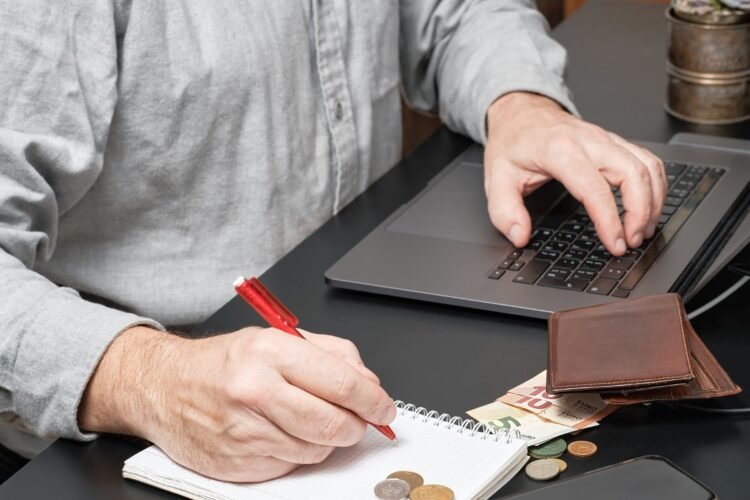 businessman-accountant-holding-pen-working-desk-using-laptop-calculate-financial-report