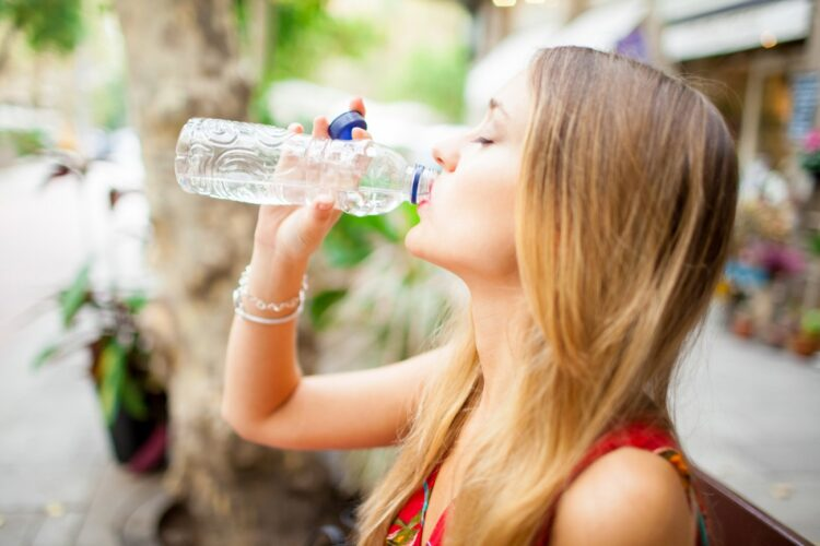 tired-female-tourist-drinking-water-outdoors