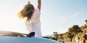 woman-car-road-trip-waving-out-window-smiling