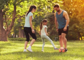 parents-daughter-play-football-in-park