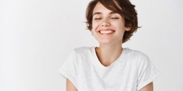 Beautiful caucasian woman dreamy smiling with eyes closed, standing relaxed and happy against white background. Copy space